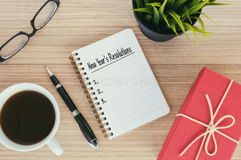 New Year`s Resolutions text on notepad. Gift box,eyeglasses, coffee, pen, pot plant royalty free stock photography