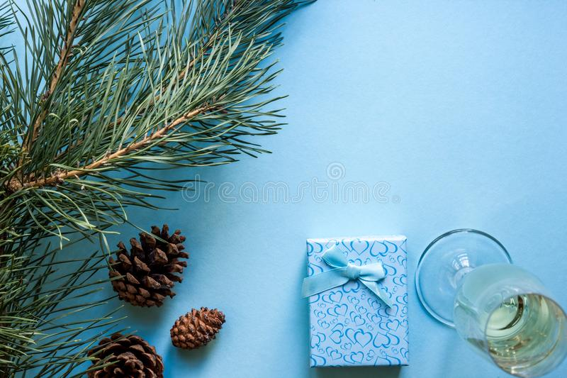 New Year`s still life - a glass of champagne, Christmas decorations and spruce branches on blue background royalty free stock images