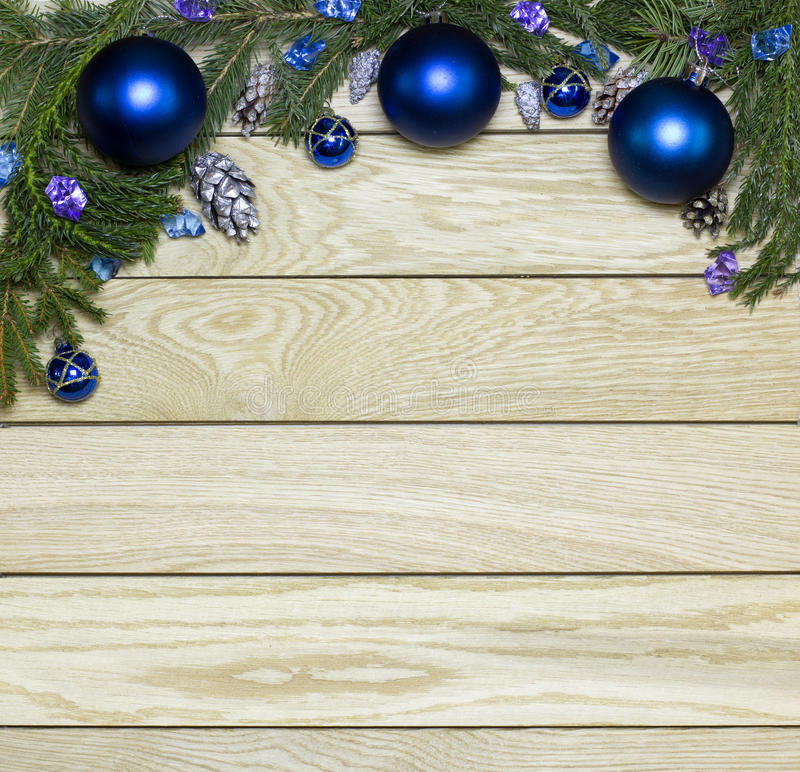 New Year`s top border frame. Christmas wooden background. New Year`s top border, frame from Christmas tree fir branches, silver pine cones, blue balls on royalty free stock photography