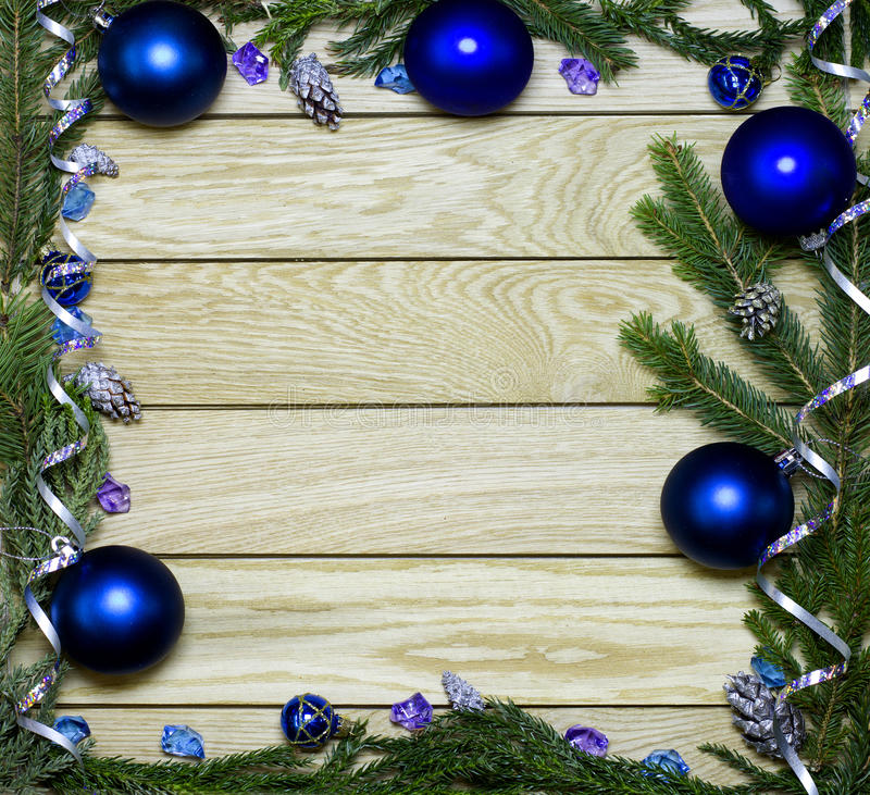 New Year`s top border frame. Christmas wooden background. New Year`s border frame from Christmas tree fir branches, silver pine cones, ribbons, blue balls on royalty free stock images