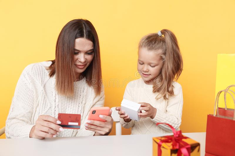 New Year shopping online concept. Mother showing daughter something on the phone. New Year shopping online concept. Mother showing daughter something on the stock photos