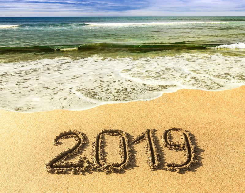 New 2019 year in the South, the sea. Sea surf. Blue wave is coming ashore. Inscription on sand, celebrate new year in the tropics. royalty free stock images