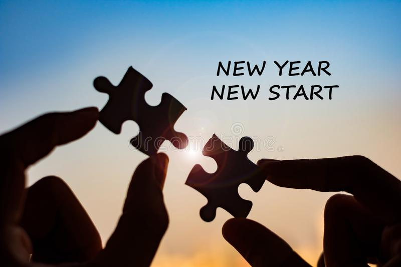 New Year New Start word with hands connecting couple puzzle piece against sunrise effect, businesswoman holding jigsaw with sunset. Background. Business stock photography