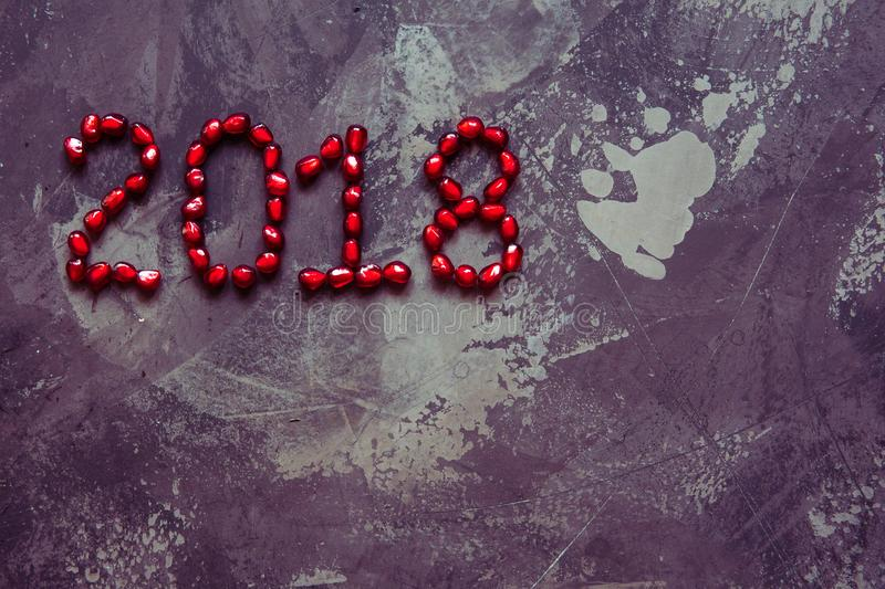 New year 2018 text pomegranate seeds top view stock photo
