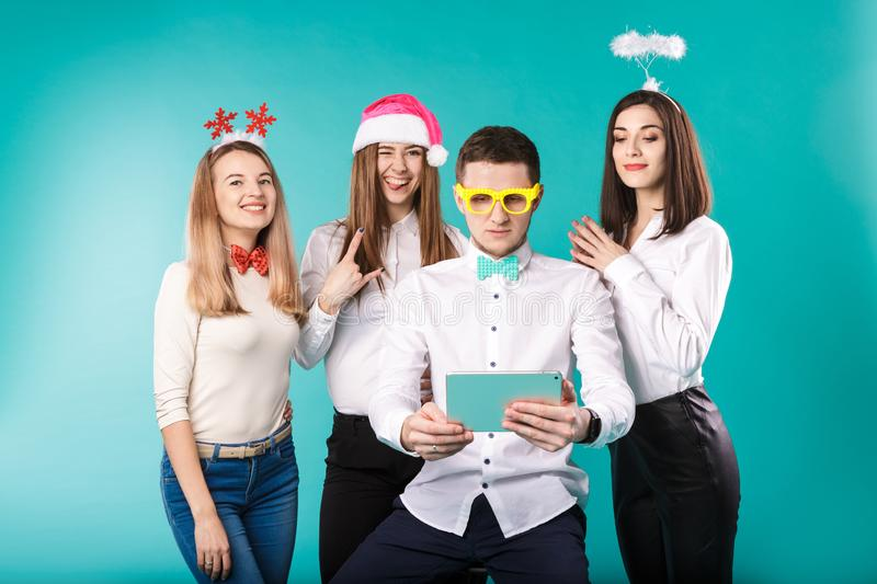 New Year theme Christmas winter office company employees. Group 4 young Caucasian people business smile holiday funny hats royalty free stock photos