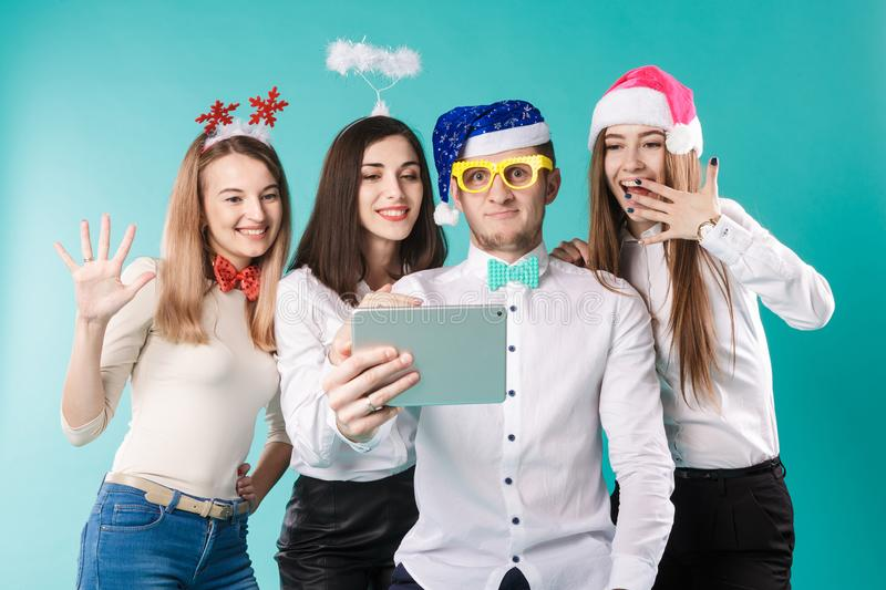 New Year theme Christmas winter office company employees. Group 4 young Caucasian people business smile holiday funny hats stock photo