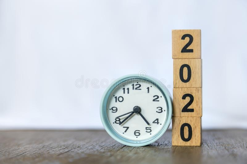 2020 new year and time concept. Close up of round clock and stack of wood number blocks on wooden table and white background royalty free stock photography