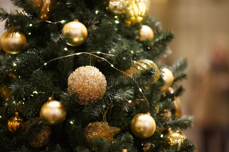 New Year tree with ornaments. New Year tree with gold ornaments on blurred background royalty free stock images