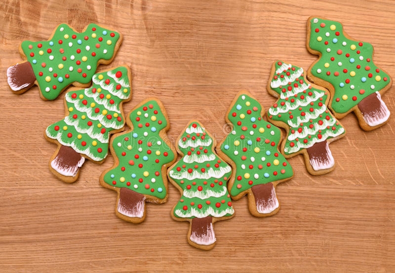New year trees cookies on wooden background, free space, flat. Green new year tree cookies on wooden background, flat stock photography