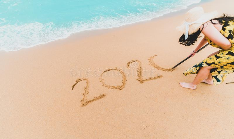 2020 New Year. 2020 woman written on sandy beach with wave foam at sea beach. Happy New Year. Tropical celebration.New Years stock photos