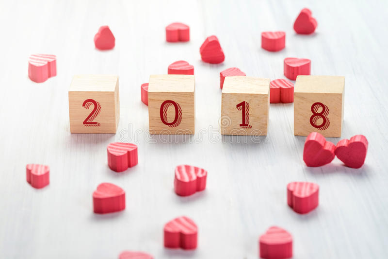 2018 new year on wood cube with group of mini red heart on white stock images