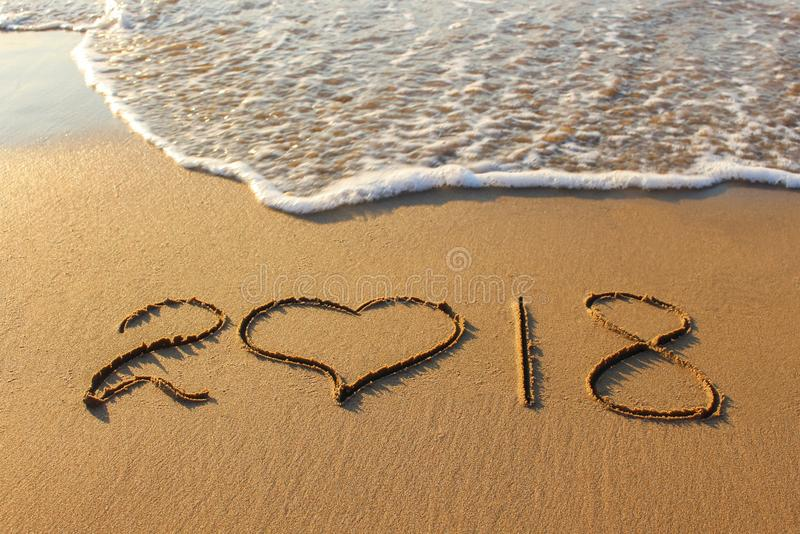 2018 new year written on sandy beach stock images