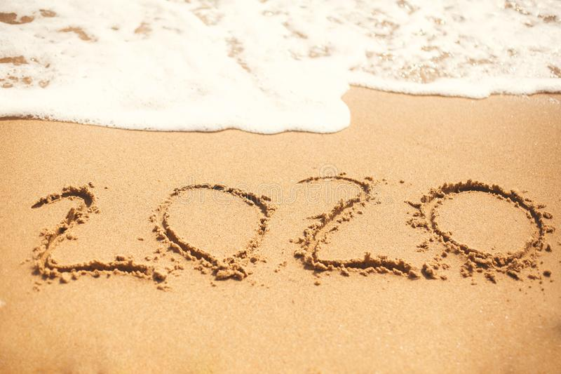 2020 New Year. 2020 written on sandy beach with wave foam at sea beach. Happy New Year. Tropical celebration. Inscription on royalty free stock photo