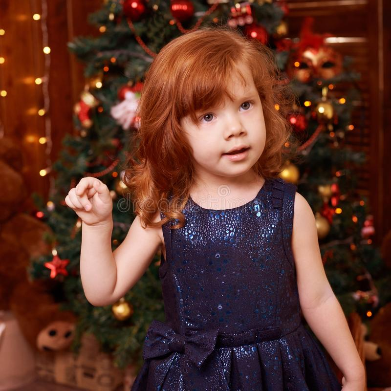 New Year xmas child. Christmas eve holiday. Beautiful little girl. Christmas interior. Blue dress stock photography