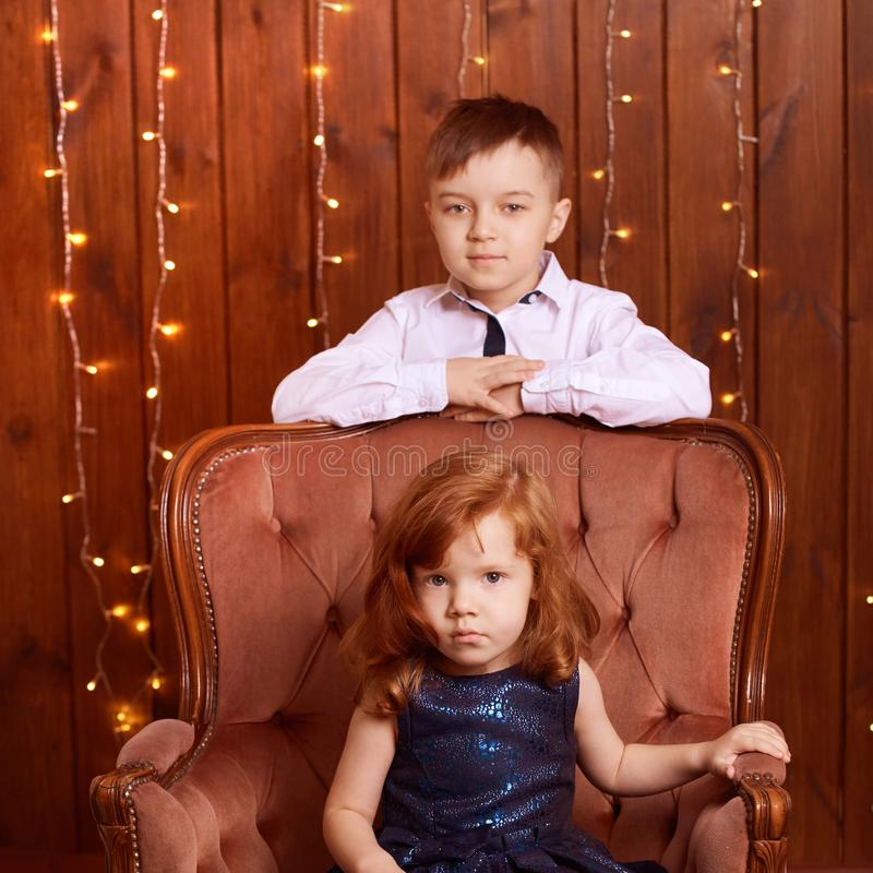 New Year xmas child. Christmas eve holiday. Brother and sister. Big chair. Blue dress. Small children stock photos