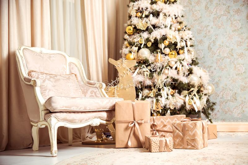 New Years or Christmas interior with a fir tree, vintage chair and gifts under Christmas tree stock photography