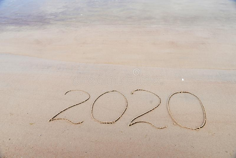 New Years 2020 concept. Handwritten inscription 2020 on beautiful sand beach. Lettering on beach with wave and clear royalty free stock image