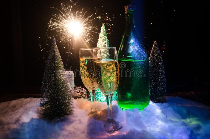 New Years Eve celebration background with pair of flutes and bottle of champagne with christmas tree on snow on dark background. stock images