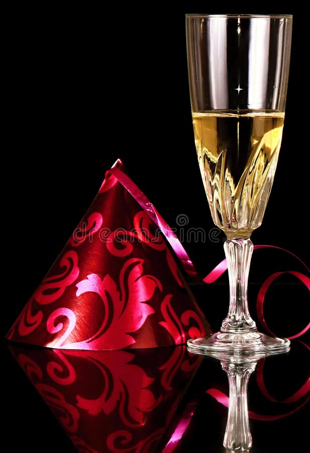 New years eve celebration with glass of champagne and party hat stock photo