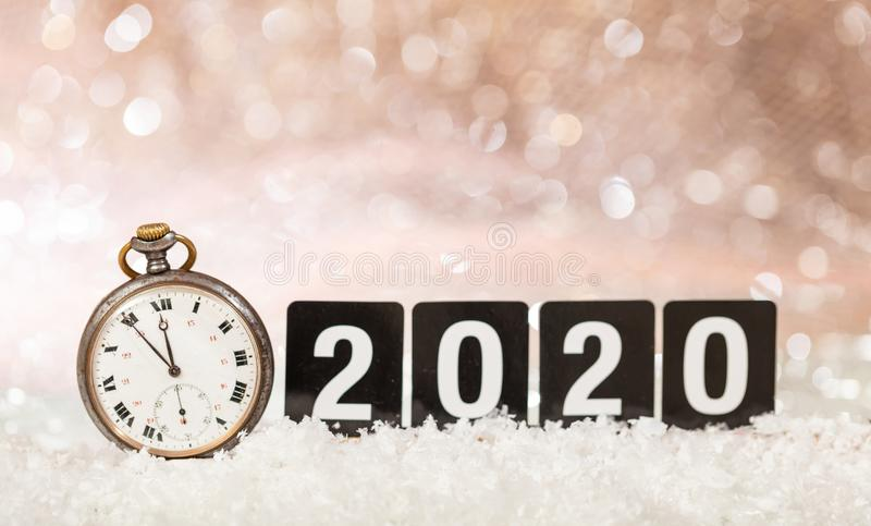 2020 New Years eve celebration. Minutes to midnight on an old watch, bokeh festive. Background stock image