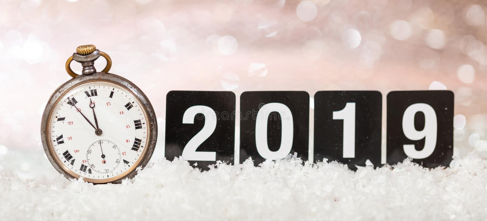 2019 New Years eve celebration. Minutes to midnight on an old watch, bokeh festive background stock image