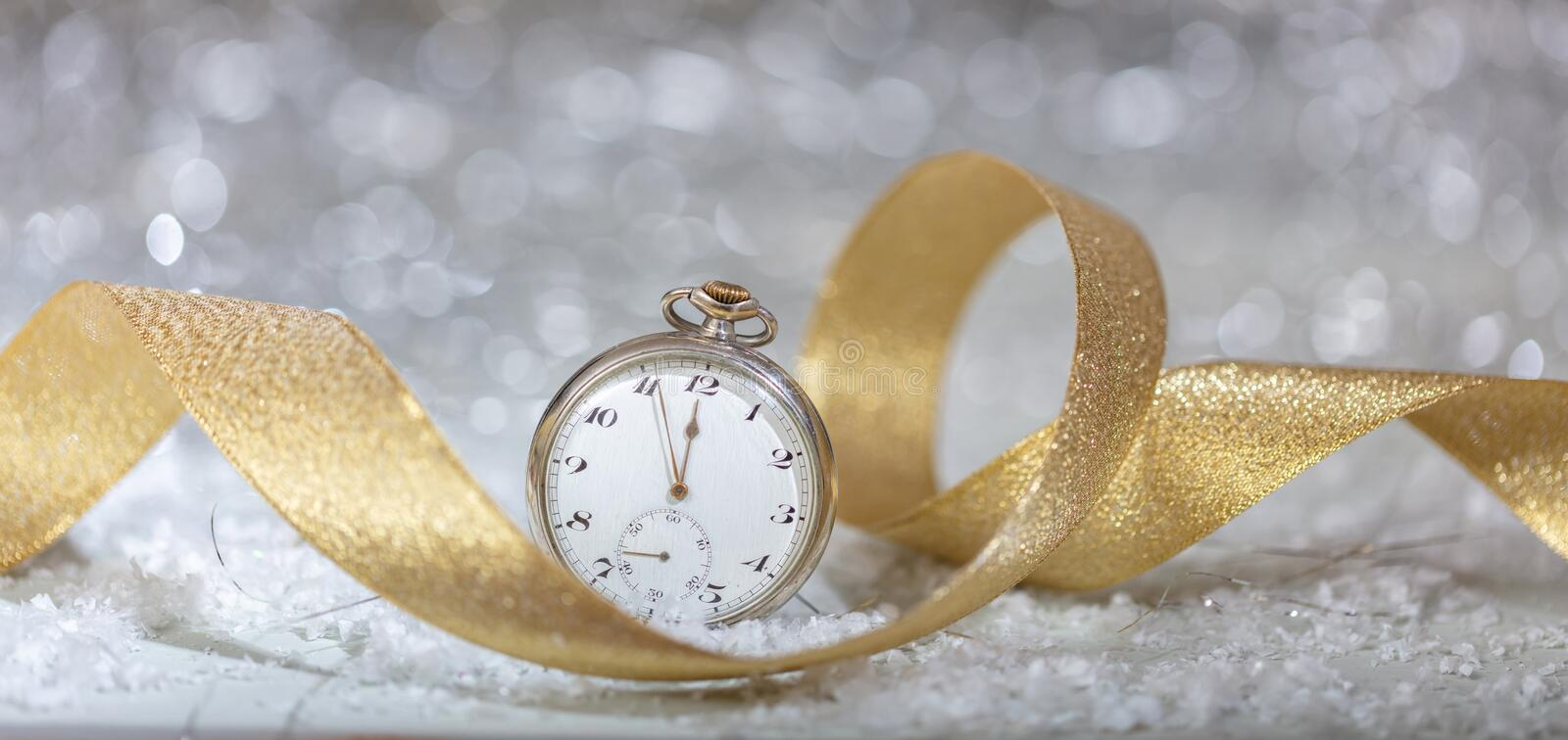 New Years eve celebration party. Minutes to midnight on an old watch, bokeh festive background royalty free stock image