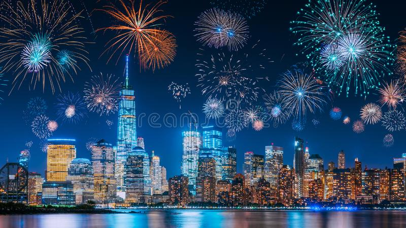 New Years Eve with colorful Fireworks over New York City skyline long exposure with beautiful dark blue sky, sci-fi orange city stock photos