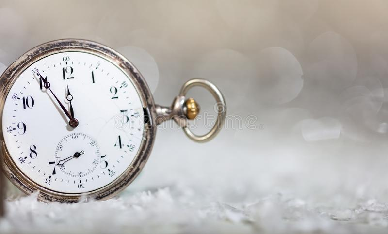 New Years eve countdown. Minutes to midnight on an old fashioned pocket watch, bokeh background. Copy space stock photos