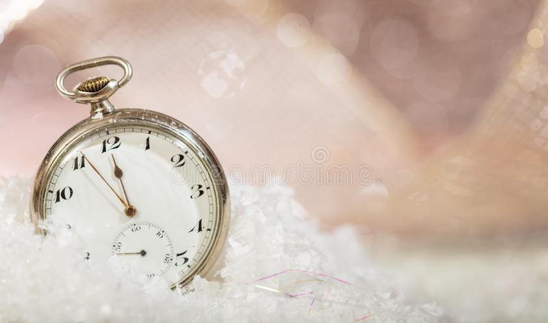 New Years eve countdown. Minutes to midnight on an old fashioned pocket watch, bokeh snowy background stock images