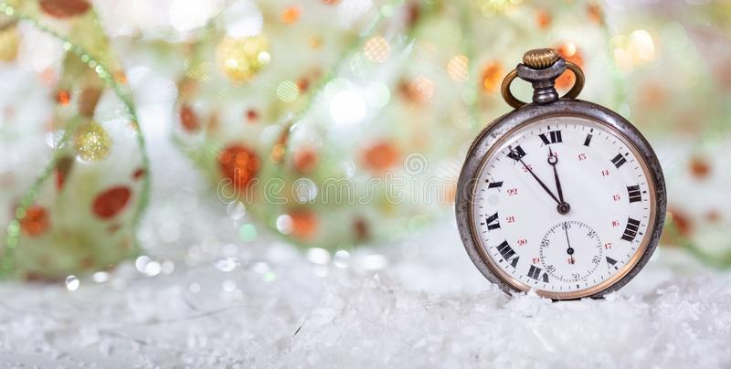 New Years eve countdown. Minutes to midnight on an old watch, bokeh background. Copy space royalty free stock photo