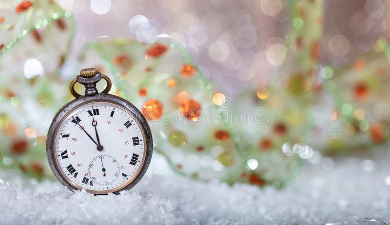 New Years eve countdown. Minutes to midnight on an old watch, bokeh background. Copy space stock photos