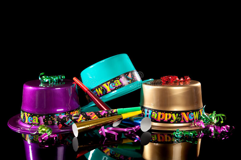 New years eve hat and noisemakers on black. Colored New Years Eve hats including green, purple, pink gold and red, streamers, noise makers and confetti on a royalty free stock image