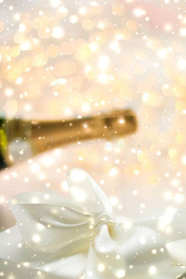 New Years Eve holiday champagne bottle and a gift box and shiny snow on marble background. Christmas time, happy holidays and luxury present concept - New Years royalty free stock photos