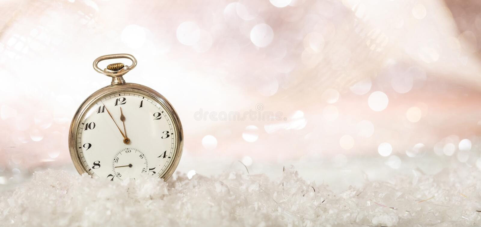 New Years eve party celebration. Minutes to midnight on an old fashioned pocket watch, bokeh snowy background, copy space. Banner royalty free stock photography