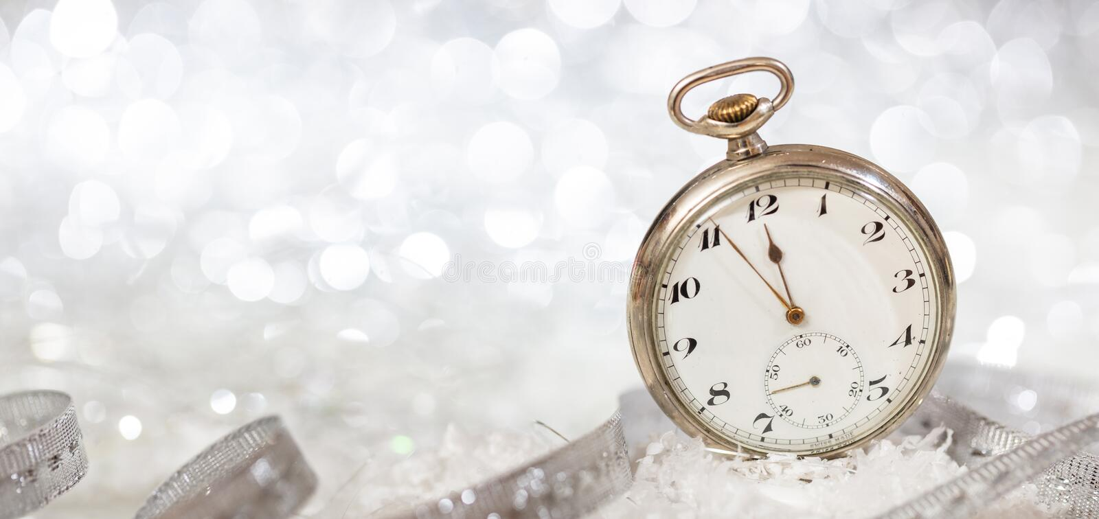 New Years eve party celebration. Minutes to midnight on an old fashioned watch, bokeh festive background royalty free stock photo