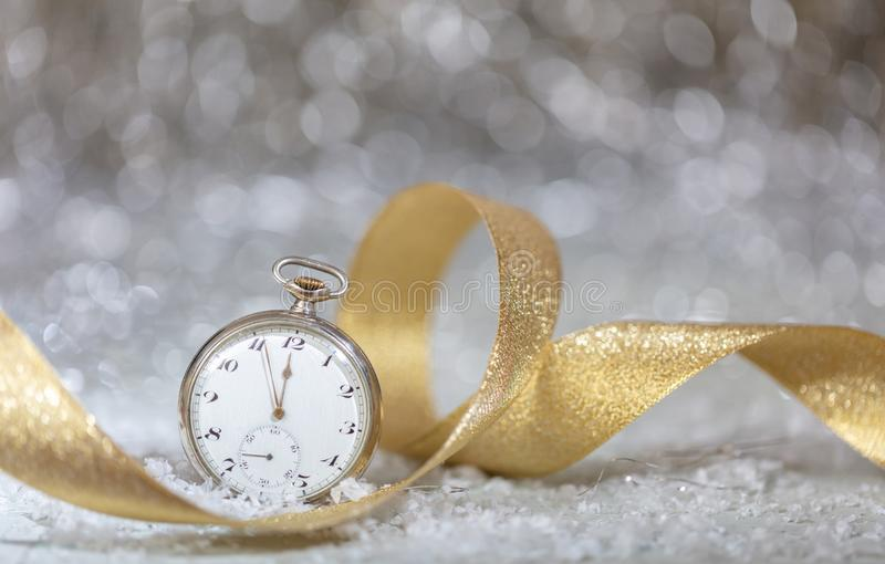 New Years eve party celebration. Minutes to midnight on an old fashioned watch, bokeh festive stock photography