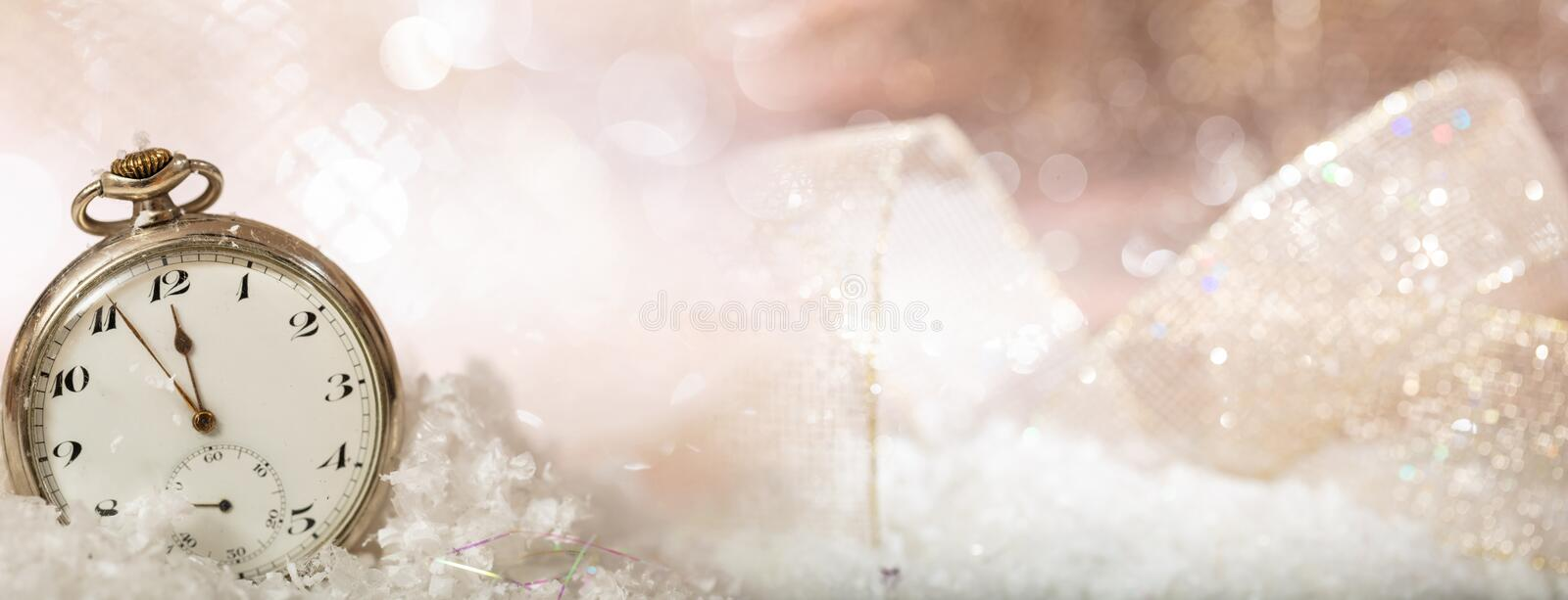 New Years eve party celebration. Minutes to midnight on an old watch, bokeh festive background. Banner royalty free stock images