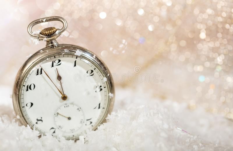 New Years eve party celebration. Minutes to midnight on an old watch, bokeh snowy background. Copy space royalty free stock photography