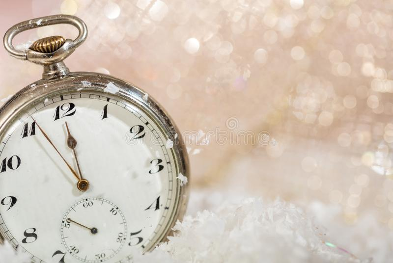 New Years eve party celebration. Minutes to midnight on an old watch, bokeh snowy background. Copy space stock image
