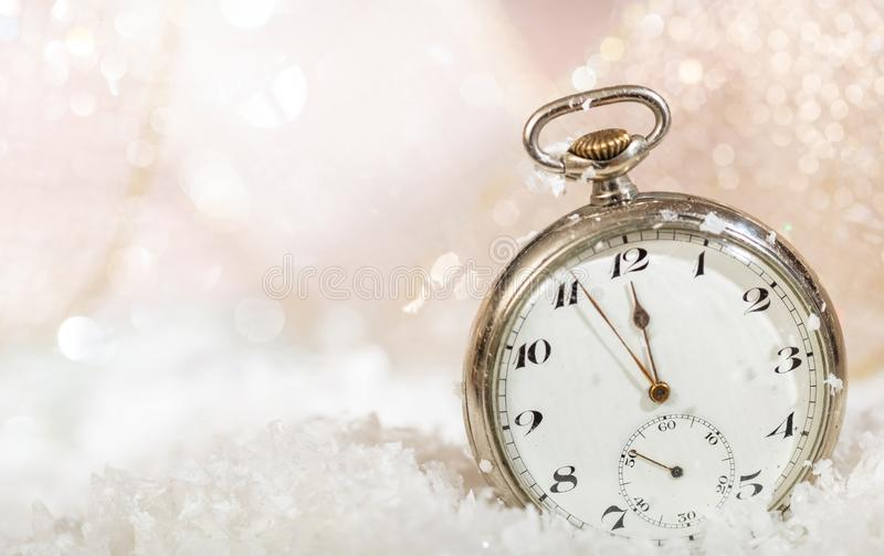 New Years eve party celebration. Minutes to midnight on an old watch, bokeh snowy stock images