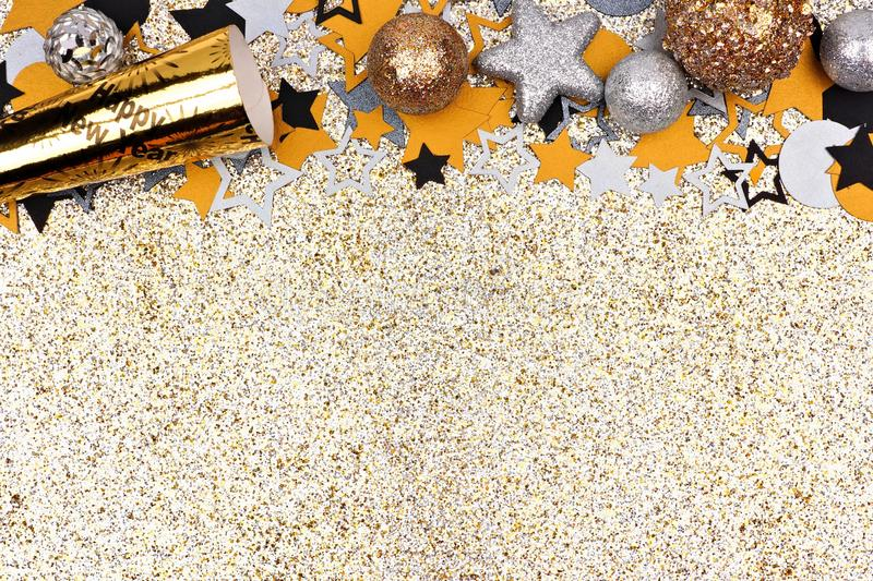 New Years Eve top border against glittery gold background. New Years concept top border with confetti, baubles and party noisemaker against a glittery gold royalty free stock photos