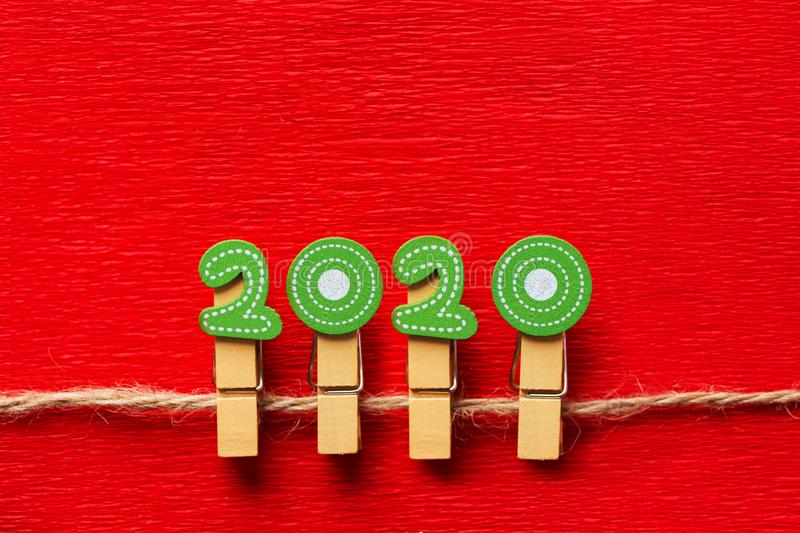 New Years festive greeting card banner poster calendar template numbers 2020 on wooden clips on twine crimson red background stock photos