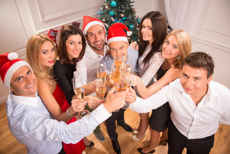 New Years party. Half-length portrait of the company of happy young smiling friends standing together drinking the champagne greeting us with the New Year. Top royalty free stock image
