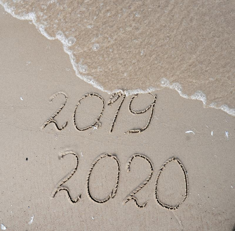 New Years 2020 replace 2019 concept. Handwritten inscription 2019 and 2020 on beautiful sand beach. End of 2019 Happy stock photography