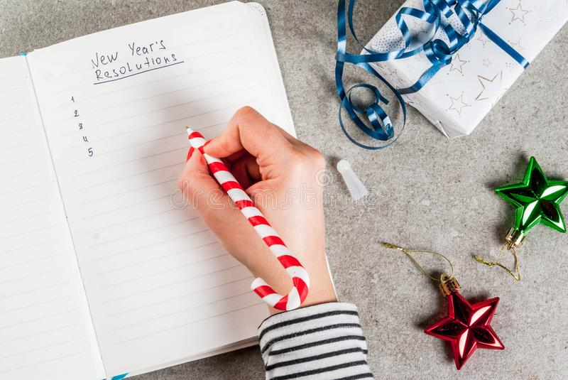 New years resolutions concept. Girl writing new years resolutions, hands in picture, open notebook on a grey stone table table. with christmas gift, pen and royalty free stock photography