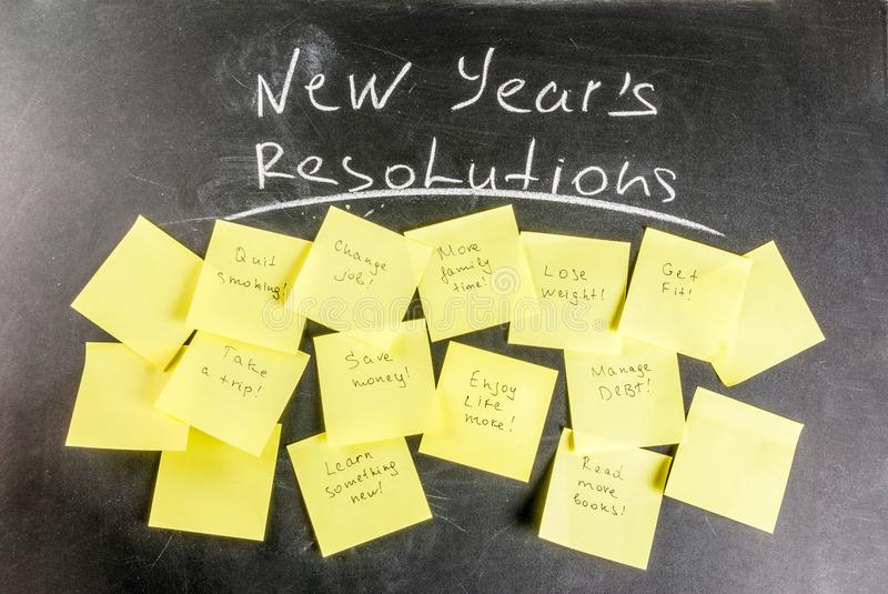 New years resolutions concept. New years resolutions, blackboard background with chalk and colorful sticky notes with popular new year resolutions, copy space royalty free stock images