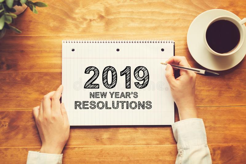 2019 New Years Resolutions with a person holding a pen. On a wooden desk royalty free stock photography
