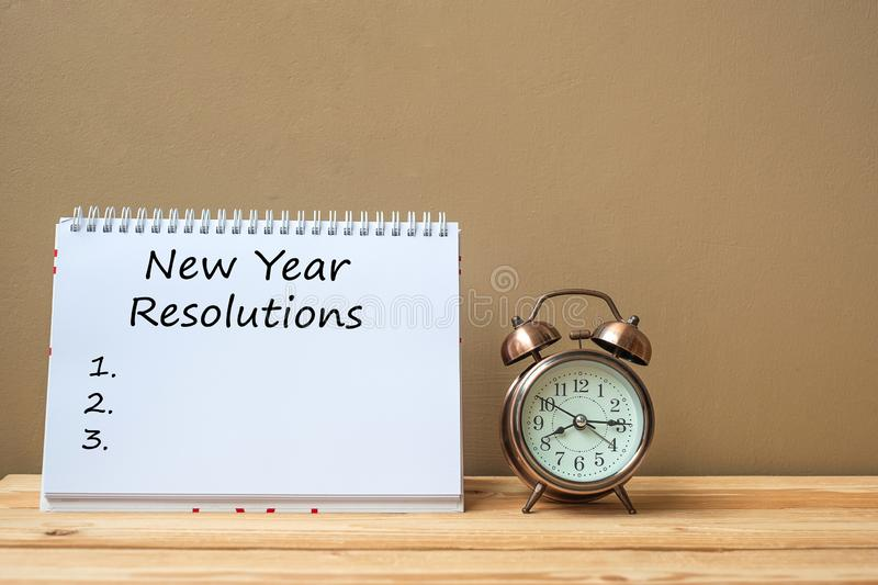 New years Resolutions text on notebook and retro alarm clock on table and copy space. Goals, Mission and New Start royalty free stock images