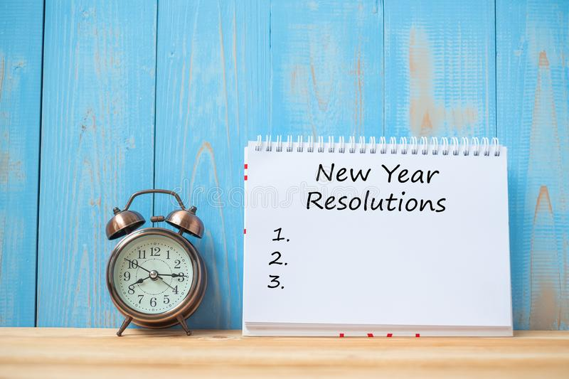 New years Resolutions text on notebook and retro alarm clock on table and copy space. Goals, Mission and New Start royalty free stock image