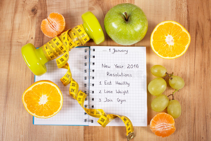 New years resolutions written in notebook and dumbbells with centimeter. New years resolutions eat healthy, lose weight and join gym written in notebook stock image